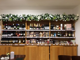 Green and silver garland above wine selection
